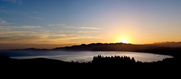 Panoramic view of ocean, mountain, trees and colorful sky stock photos