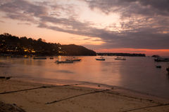 Sunset on Nusa Lembongan. With boats and the village in the background Royalty Free Stock Image