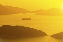 Sunset ocean along mountains with moving ships Royalty Free Stock Photo