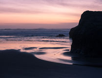 Sunset on ocean beach with cliffs Stock Image