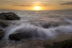 Sunset Ocean Beach Wave Breaking on Rocks Stock Photography