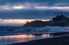 Sunset at ocean cape. Sunset on a cloudy day at Cape Kiwanda State Park, Oregon with the ocean waves and sandy beach Royalty Free Stock Images
