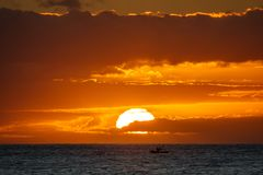 Sunset in the ocean with fishing boat. Long shot of orange sunset in the ocean with fishing boat royalty free stock image