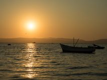 Sunset by the ocean. Orange sunset by the ocean in Paracas, Peru, with some anchored small fishing boats and seagulls flying in the orange sky stock photo