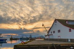 Sunset on the ocean at the pier of fishing ships. A wooden pier and a warehouse royalty free stock photos