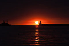 Sunset on the ocean. Red sunset on the ocean on a background of ships royalty free stock photos