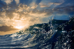 Sunset Ocean Rip Curl Wave. An ocean sunset shorebreak in side view with bokeh flares. Big beautiful high contrast sunrise wave swirling. Bright sun shining on Stock Images