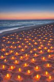 Sunset ocean sandy beach decorated with lot flare lights of cand Stock Image