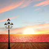 Sunset ocean scenery with wooden boardwalk and lantern. Romantic sunset ocean scenery with wooden boardwalk and lantern Stock Photos