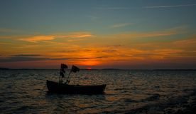 Sunset boat. Sunset at ocean with silhouette of boat Stock Images