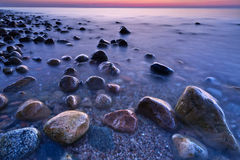 Sunset ocean stones. Baltic Sea coast, Poland. Royalty Free Stock Photo