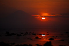 Sunset on the ocean - view of volcano Batur. Indonesia, Bali. Royalty Free Stock Images