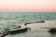 Sunset by the ocean. With waves and the shores Stock Images