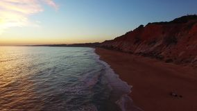 Sunset at oceanside cliffs beach aerial Portugal Algarve aerial view stock video footage