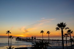 Sunset by Oceanside Pier, Palms and the Pacific Oceanin the famous surf city in California USA. Sunset by Oceanside Pier, Palms and the Pacific Oceanin the stock images