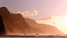 Sunset off coastline on Kauai with a stormy sea. Receding headlands of Kauai coastline illuminated at sunset over a stormy sea with a distant bird stock image