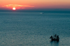 Sunset in Oia. Of Santorini with ship passing by in the foreground Royalty Free Stock Image
