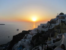 Sunset in Oia, Santorini, Greece. On a cloudless evening, the sun slowly sets into the Aegean Sea with the village of Oia in the foreground Royalty Free Stock Photo