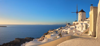 Sunset in Oia village on Santorini island, Greece. Beautiful Santorini island in Greece. Traditional apartments and windmills in Oia village on a sunset Stock Photography