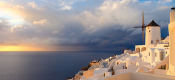 Sunset in Oia village on Santorini island, Greece. Beautiful Santorini island in Greece. Traditional apartments and windmills in Oia village on a sunset Royalty Free Stock Photography