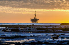 Sunset and oil rig Stock Images
