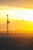 Sunset on an oilrig and the Rocky Mountains. Oilrig drilling at sunset under Longs Peak in the Rocky Mountains Royalty Free Stock Image