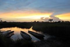 Sunset in Okavango Delta. Okavango Delta with Mokoros at sunset Stock Images