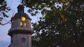 Sunset and old clock tower in the city center of Varna, Bulgaria. Popular city landmark.  stock video