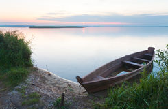 Sunset with old flooding boat on summer lake shore Royalty Free Stock Image