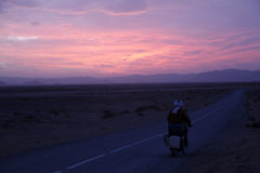 Sunset. One man on a motorbike is travelling the road in morocco Stock Photos