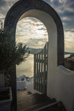 Sunset through open gate in Oia town, Santorini island, Greece. Sunset and seascape through open gate in Oia town, Santorini island, Greece Stock Images