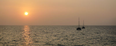 Sunset on the open sea with the silhouettes of the boat and catamaran. Panorama photo with the sunset reflection over the sea with the silhouettes of the boat Stock Photos