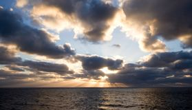 Sunset on open seas. Cloudy sunset with sun rays peaking through royalty free stock image