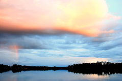 Sunset Orange Cloud. Orange and red rain cloud at Sunset over a lake in Finland, Scandinavia royalty free stock images