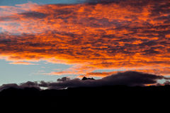 Sunset with orange clouds. Over the mountains Royalty Free Stock Images