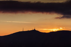 Sunset orange sky on Col Visentin mountain summit. With tv and radio antennas, Veneto, Italy Stock Images