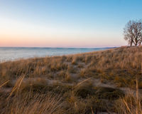 Sunset at Oval Beach Saugatuck. Michigan in spring of 2015 with calm waves and clear sky stock image