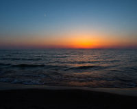 Sunset at Oval Beach Saugatuck. Michigan in spring of 2015 with calm waves and clear sky stock photography
