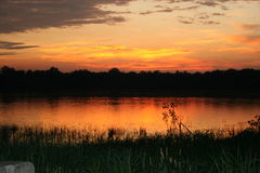 Sunset on an oval lake. Beautiful colors of orange and yellow on an oval shape lake Stock Photography