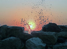 Sunset over the Aegean Sea. Black rocks splashing water Royalty Free Stock Images