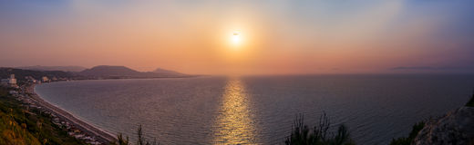Sunset over the Aegean Sea at Rhodes. A plane passes ver the sun on its way in to land on Rhodes stock photography