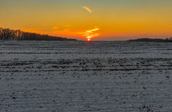 Sunset over agricultural field at winter season Royalty Free Stock Photo