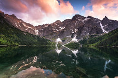 Sunset over alpine pond Morskie Oko in Poland. Mirror reflection on water surface royalty free stock photo