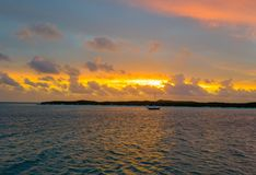 Free Sunset Over An Island In Bahamas And A Sailing Boat Sailing In The Ocean Royalty Free Stock Photo - 124582945