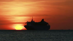 Sunset over the Andaman sea with a cruise ship sailing off into the horizon stock footage