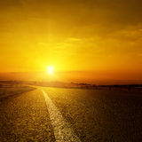 Sunset over asphalt road Stock Photo