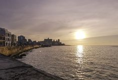 Sunset over Atlantic Ocean with residential building in background - Havana, Cuba. Sunset over Malecon and Atlantic Ocean with residential building in background Stock Images