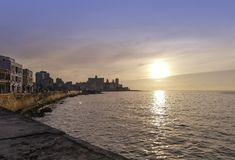 Sunset over Atlantic Ocean with residential building in background - Havana, Cuba. Sunset over Malecon and Atlantic Ocean with residential building in background Royalty Free Stock Photography