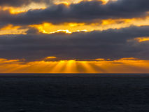 Sunset over the Atlantic ocean with sun breaking trough clouds. Royalty Free Stock Photos