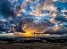 Sunset over the Atlantic ocean with sun breaking trough clouds. Royalty Free Stock Photo